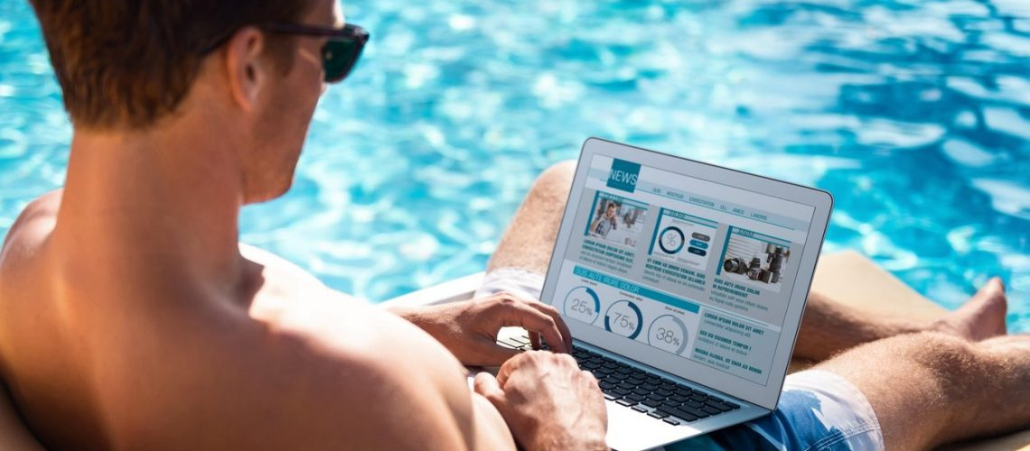 Search for information. Delighted pleasant man lying on the sun bed and using laptop while relaxing near swimming pool,Image: 298674697, License: Royalty-free, Restrictions: , Model Release: yes