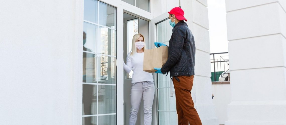 delivery man in protective mask and medical gloves holding a paper box. Delivery service under quarantine, disease outbreak, coronavirus covid-19 pandemic,Image: 537903026, License: Royalty-free, Restrictions: , Model Release: no, Credit line: Profimedia